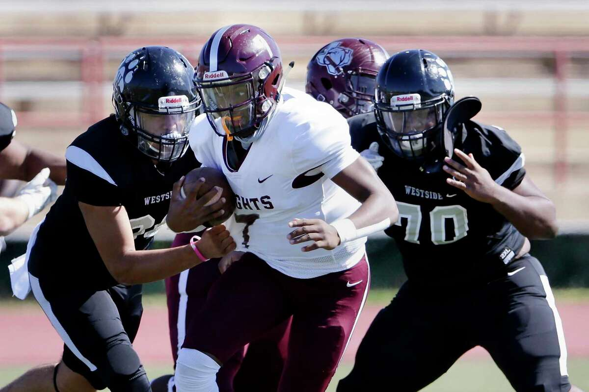 Heights quarterback Jalen Morrison (7) pushes past Westside defenders Kevin Soto, left, and Jared Gay (70) during their game at Butler Stadium Saturday, Oct. 31, 2020 in Houston, TX.