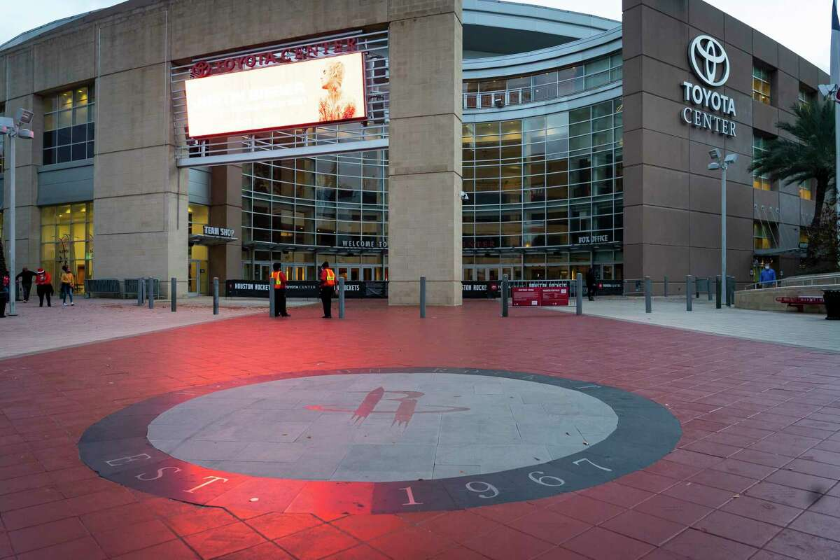 People stand in front of Toyota Center after it was announced that the Rockets opening night game against the Oklahoma City Thunder was being postponed, Wednesday, Dec. 23, 2020, in Houston.