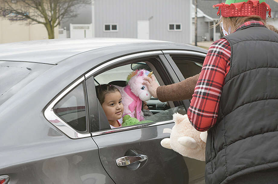 A child awaits a stuffed animal being handed out Wednesday by Beardstown city officials and City Public Works at Fourth and State streets, near the Old Smoke shop. Photo: Rochelle Eiselt | Journal-Courier