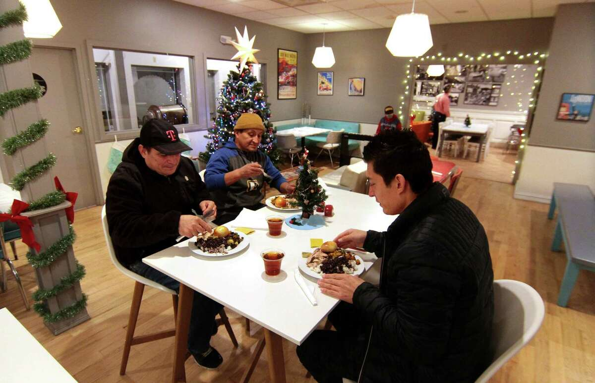 Jacinto Andrade, left, has a pre-Christmas dinner with his son Diego and friend Jose Chavez at Mothership Bakery & Cafe in Danbury, Conn., on Wednesday Dec. 23, 2020. The cafe held the dinner for area homeless, day laborers and anyone in need. Volunteers from the food pantry Jericho helped bring in the guests for the dinner and staff at Mothership prepared and served the meals.