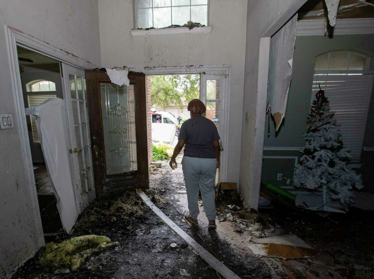 Catherine Modlies takes a look at her Christmas tree after checking her burned house Wednesday, Dec. 23, 2020, in Cypress. Modlies, a mother of 11, vacuated the house fire with 10 children at 3 a.m. She said she was grateful that all of them get out of the fire safe despite of the fire destroying her rental home.