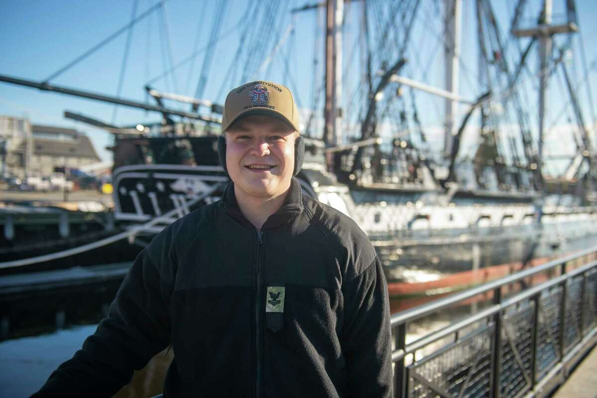 BOSTON (December 10, 2020) Culinary Specialist 2nd Class Blake Bentz poses for a picture in front of USS Constitution. The USS Constitution is the world's oldest commissioned warship afloat, and played a crucial role in the Barbary Wars and the War of 1812, actively defending sea lanes from 1797 to 1855. During normal operations, the active-duty Sailors stationed aboard USS Constitution provide free tours and offer public visitation to more than 600,000 people a year as they support the ship's mission of promoting the Navy's history and maritime heritage and raising awareness of the importance of a sustained naval presence. USS Constitution was undefeated in battle and destroyed or captured 33 opponents. (U.S. Navy Photo Illustration by Mass Communication Specialist 2nd Class Grant G. Grady/Released)