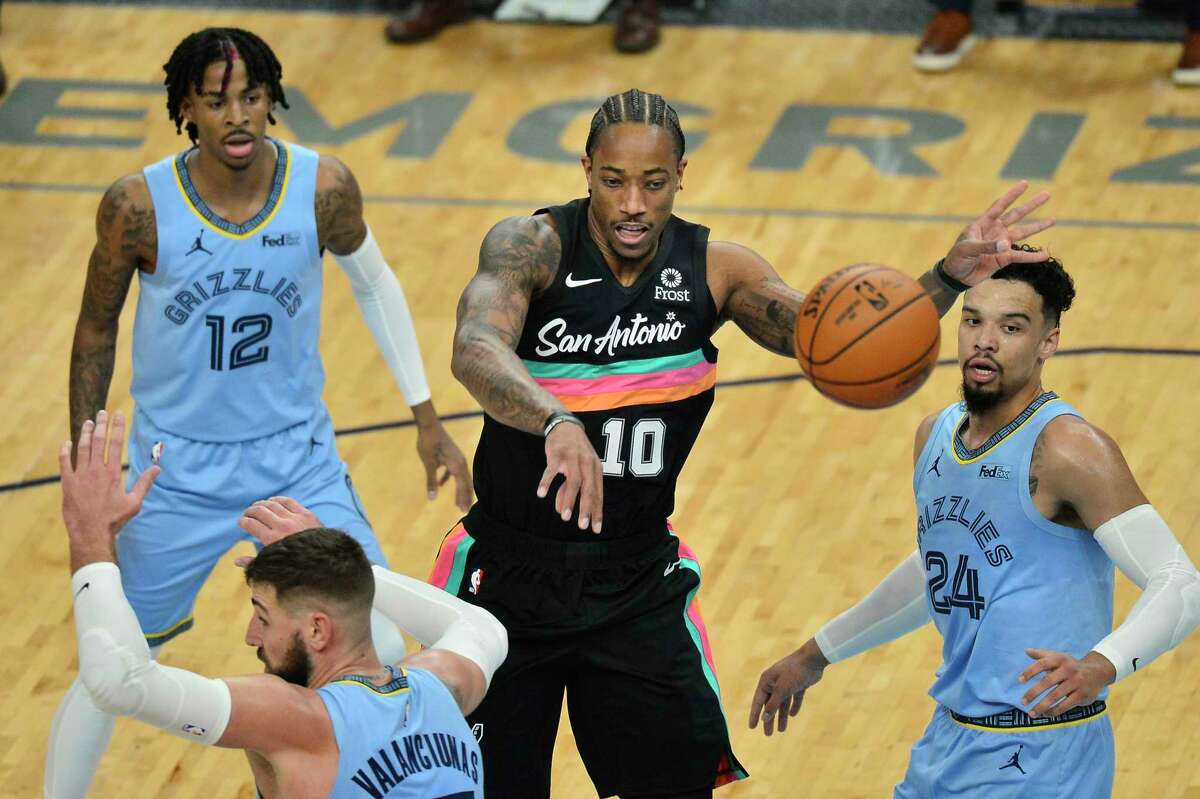 San Antonio Spurs guard DeMar DeRozan (10) passes the ball between Memphis Grizzlies guards Ja Morant (12) and Dillon Brooks (24) and center Jonas Valanciunas (17) during the first half of an NBA basketball game Wednesday, Dec. 23, 2020, in Memphis, Tenn. (AP Photo/Brandon Dill)