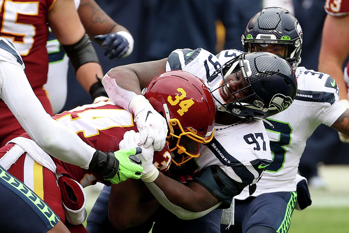 LANDOVER, MARYLAND - DECEMBER 20: Defensive tackle Poona Ford #97 of the Seattle Seahawks tackles running back Peyton Barber #34 of the Washington Football Team in the first half at FedExField on December 20, 2020 in Landover, Maryland. (Photo by Patrick Smith/Getty Images)