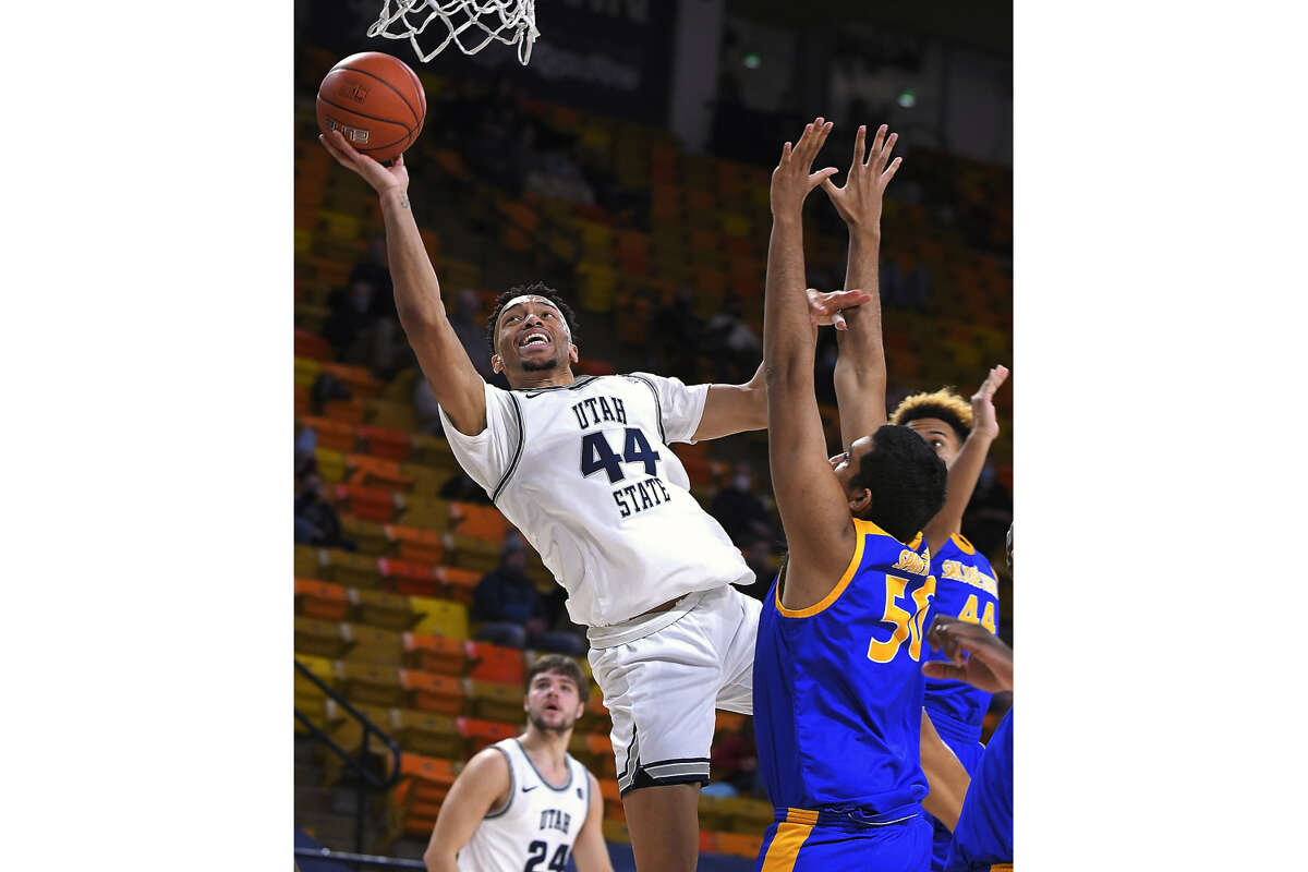 Utah State guard Marco Anthony (44) shoots as San Jose State center Harminder Dhaliwal (50) and guard Trey Smith (44) defend during the second half of an NCAA college basketball game, Wednesday, Dec. 23, 2020, in Logan, Utah. (Eli Lucero/The Herald Journal via AP)