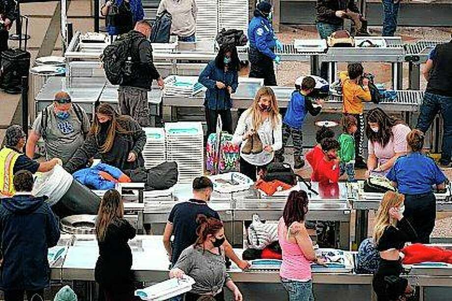 Travelers wear face masks Tuesday while passing through the south security checkpoint in the main terminal of Denver International Airport in Denver. Photo: David Zalubowski | Associated Press