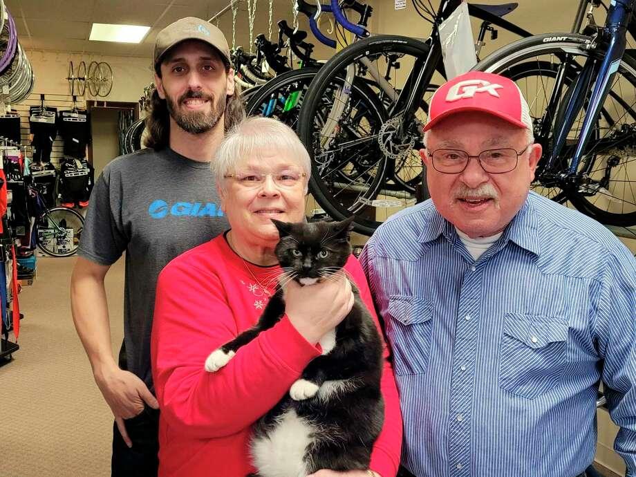 Kevin, Sondi, Odiand John Geminder. Odiis the resident cat at the store. (Photo by Ron Beacom)