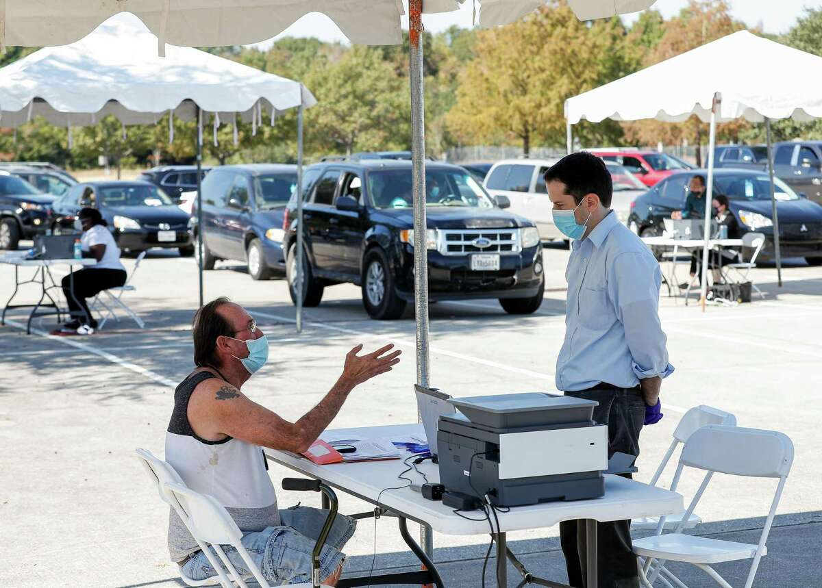 Larry Warner, left, who is facing eviction, talks to an attorney during a mobile clinic at Harvest Time Church on Friday, Nov. 6, 2020, in Houston, Texas. Harris County Precinct One Constable's Office in collaboration with the Eviction Defense Coalition hired 10 recent law school graduates to provide pro bono assistance.