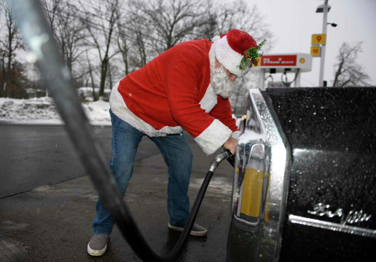 Greenwich resident Victor Samuelsen, dressed as Santa, fills up his tank at the Shell gas station in Old Greenwich, Conn. Sunday, Dec. 20, 2020.