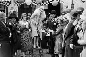 A woman pulling the cork on a bottle in 1928 at a garden party.