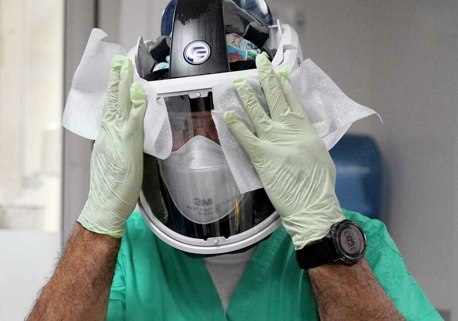 Carlos Martinez, a physical therapy technician, disinfectants his face shield after working with a COVID-19 patient in the MICU at Houston Methodist Hospital on Dec. 21, in Houston. Photo: Melissa Phillip, Staff Photographer / © 2020 Houston Chronicle