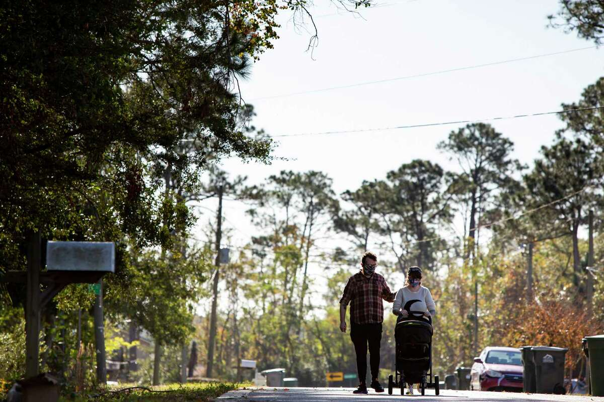 Katy Dobson and Aaron Walker take a walk with their son, Atlas, near their home in Pensacola, Fla., on Dec. 23. Atlas was conceived in the early days of the coronavirus pandemic and was born Dec. 8.