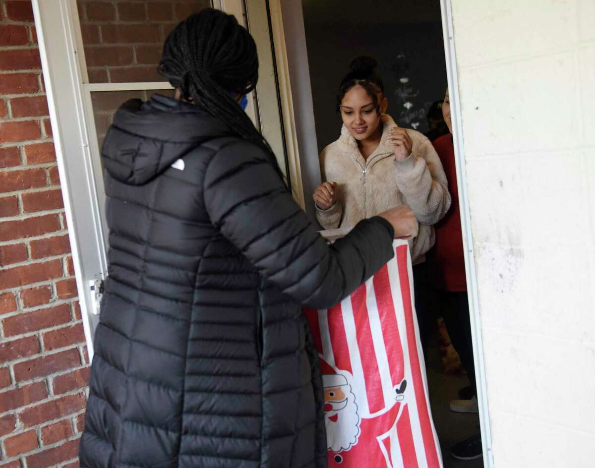 CCI social worker Vanessa Cardinal delivers holiday gifts to India Acosta, 15, and her two younger siblings at the Wilbur Peck Court public housing complex in Greenwich, Conn. Tuesday, Dec. 22, 2020. Community Centers Inc. handed out holiday gifts to 60 local children and hot meals and poinsettias to 85 local seniors. Children received gifts from donation at Round Hill Community Church via a Target gift registry, as well as clothing from Saks Fifth Avenue, and gift cards from Greenwich United Way.