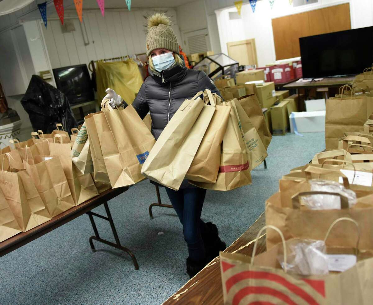 Volunteer Tara Restieri, of Greenwich, carries bagged hot meals to be delivered to local seniors from St. Roch Church in the Chickahominy section of Greenwich, Conn. Tuesday, Dec. 22, 2020. Community Centers Inc. handed out holiday gifts to 60 local children and hot meals and poinsettias to 85 local seniors. Children received gifts from donation at Round Hill Community Church via a Target gift registry, as well as clothing from Saks Fifth Avenue, and gift cards from Greenwich United Way.
