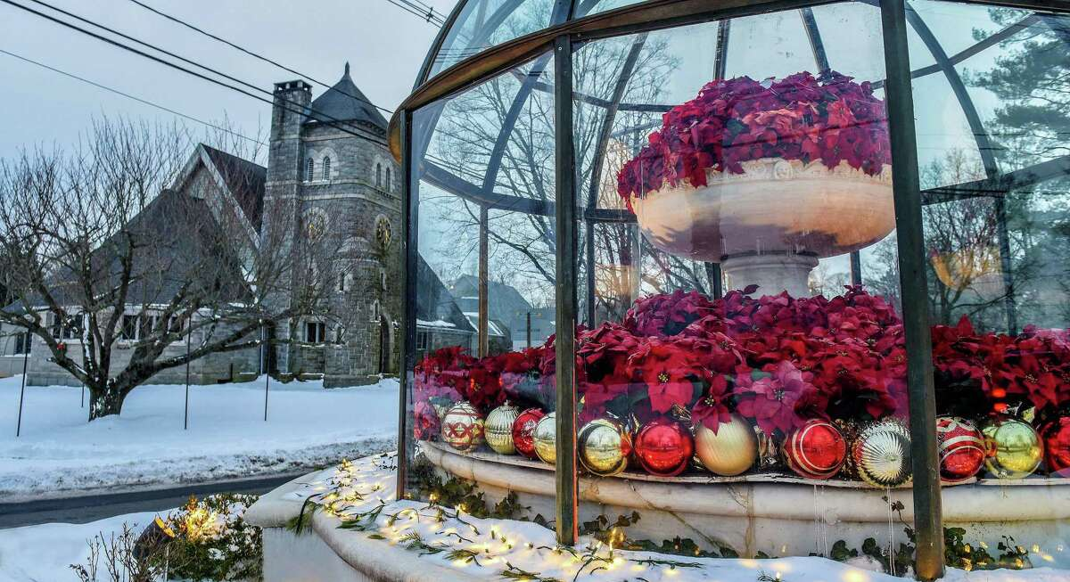 """The First Congregational Church of Ridgefield stands near the Cass Gilbert Fountain, decorated for the holidays. James T.Watson, senior minister of the church, was reminded this year of the Christmas carol and poem """"In the Bleak Midwinter"""" by C hristina Rossetti."""