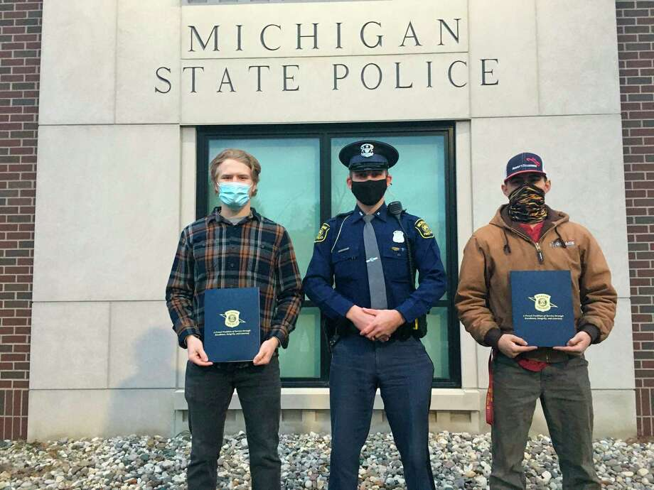 Michigan State Police trooper Christopher Kustra (center) poses with Samuel Hine and Jacob Gomola after being honored for their role in saving a man's life through CPR. (Photo provided/ Lt. Lizabeth Rich)
