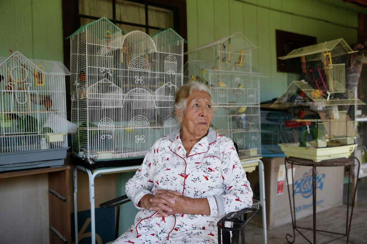 Eighty-four-year-old Juana Herrera sits with her canaries at her home in the Hoehn Drive colonia outside Edinburg, Texas, Monday, Dec. 21, 2020. Residents of the colonia and others in the area were surprised by an overdue $1,400 tax bill from the Hidalgo County Irrigation District 1, dating back to the mid-1980?•s. Herrera bought her property in the 1990?•s and was not aware of such tax that is for irrigation of farmland.