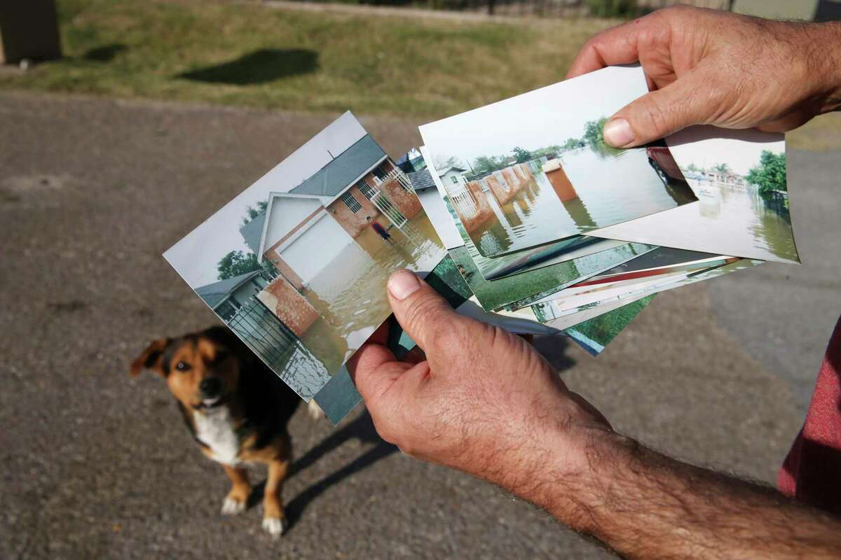 A man, who didn't want to be identified, shows photographs of past flooding in the Hoehn Drive colonia outside Edinburg, Texas, Monday, Dec. 21, 2020. In August of last year, Hidalgo County Irrigation District 1 sent residents of the colonia a tax bill of around $1,400 for 35-year-old irrigation charges the original owner of the land never paid. The starting amount is $274 but fees tacked on by the collections law firm brought the total to $1,400.