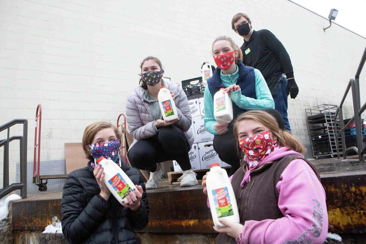 From left, Olivia Hall, Allie Davenport, Maddie Hall, Cwen Cole and others supply free milk to those in need.