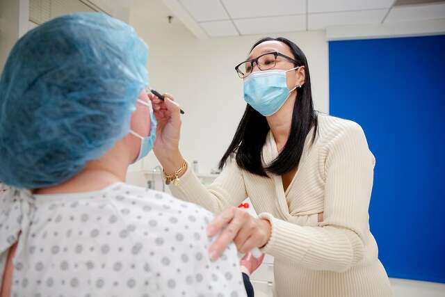 Dr. Carolyn Chang places marks on a patient's eyelids before doing a blepharoplasty at her office in San Francisco.