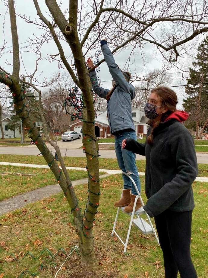 Members of the Manistee High School chapter of the National Honor Society put up Christmas decorations for a Manistee resident on Dec. 11 as part of the group's effort to serve the community. (Courtesy photo)