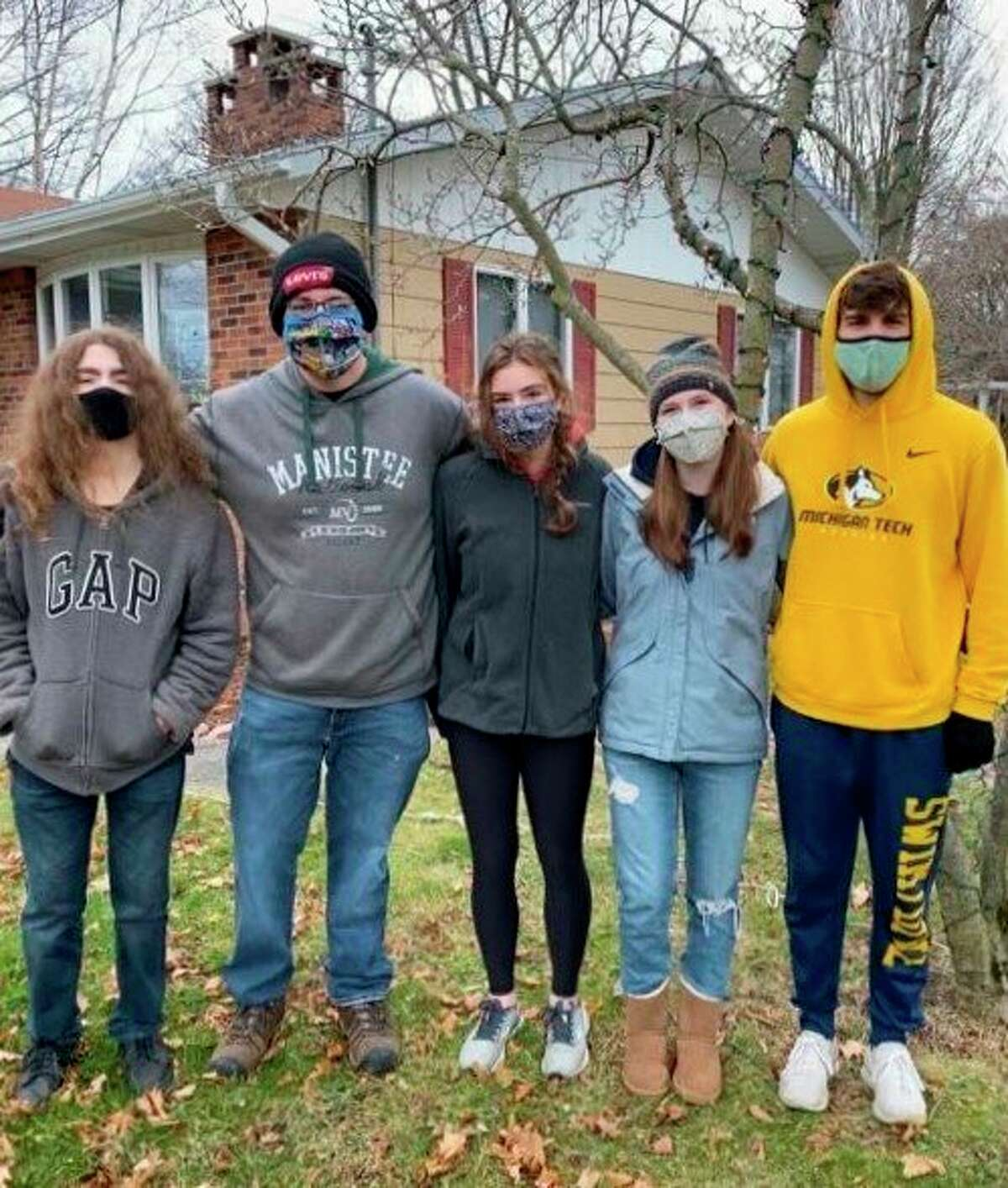 A group of students from the Manistee High School chapter of the National Honor Society take a break from putting up Christmas decorations for a Manistee resident to pose for a photo. (Courtesy photo)
