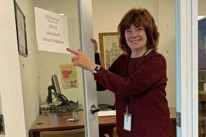"""Columnist Jacqueline Smith points to the """"welcome back"""" sign on her office door at The News-Times in Danbury. It was her first visit back since leaving in mid-March to work from home because of the pandemic. The newsroom, like many other businesses, will remain closed for the foreseeable future."""