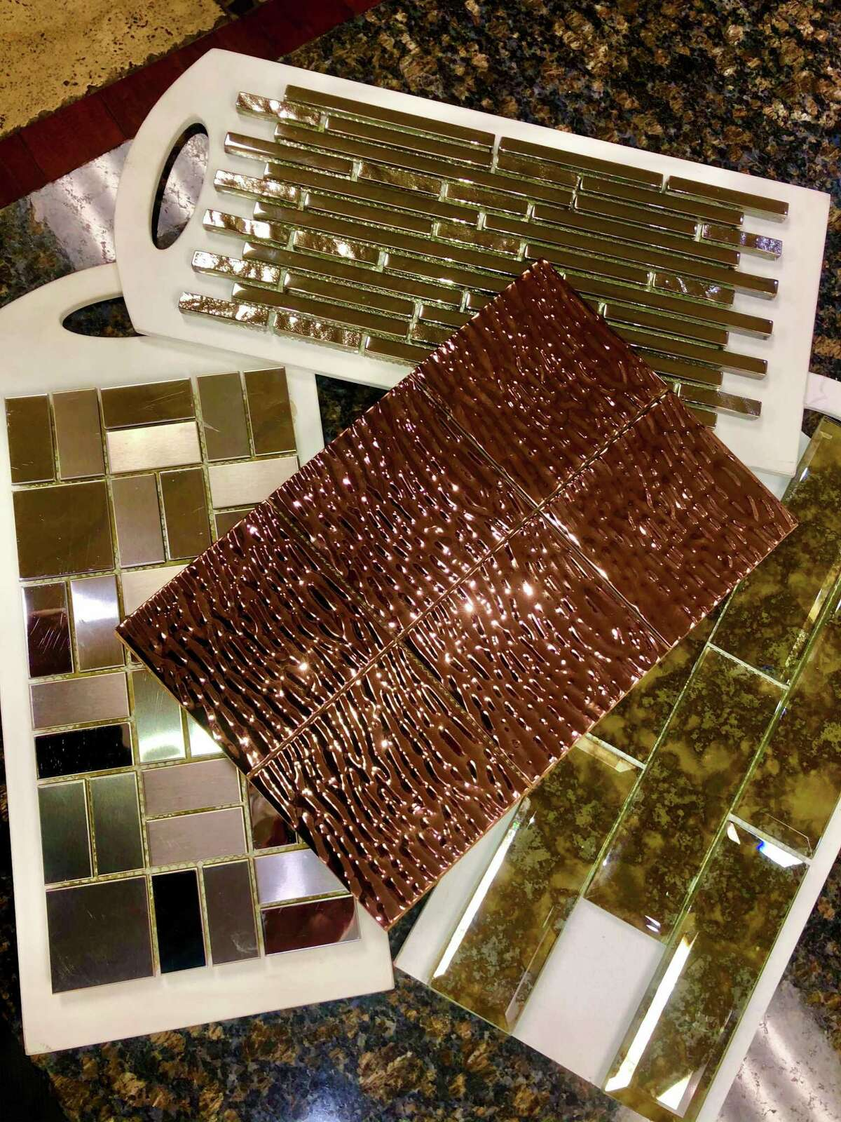 Tiles plated with various metals, such as copper, center, make for decorative flourishes on shower floors, in wall niches, for kitchen backsplashes or as simple bands along a bathroom wall.