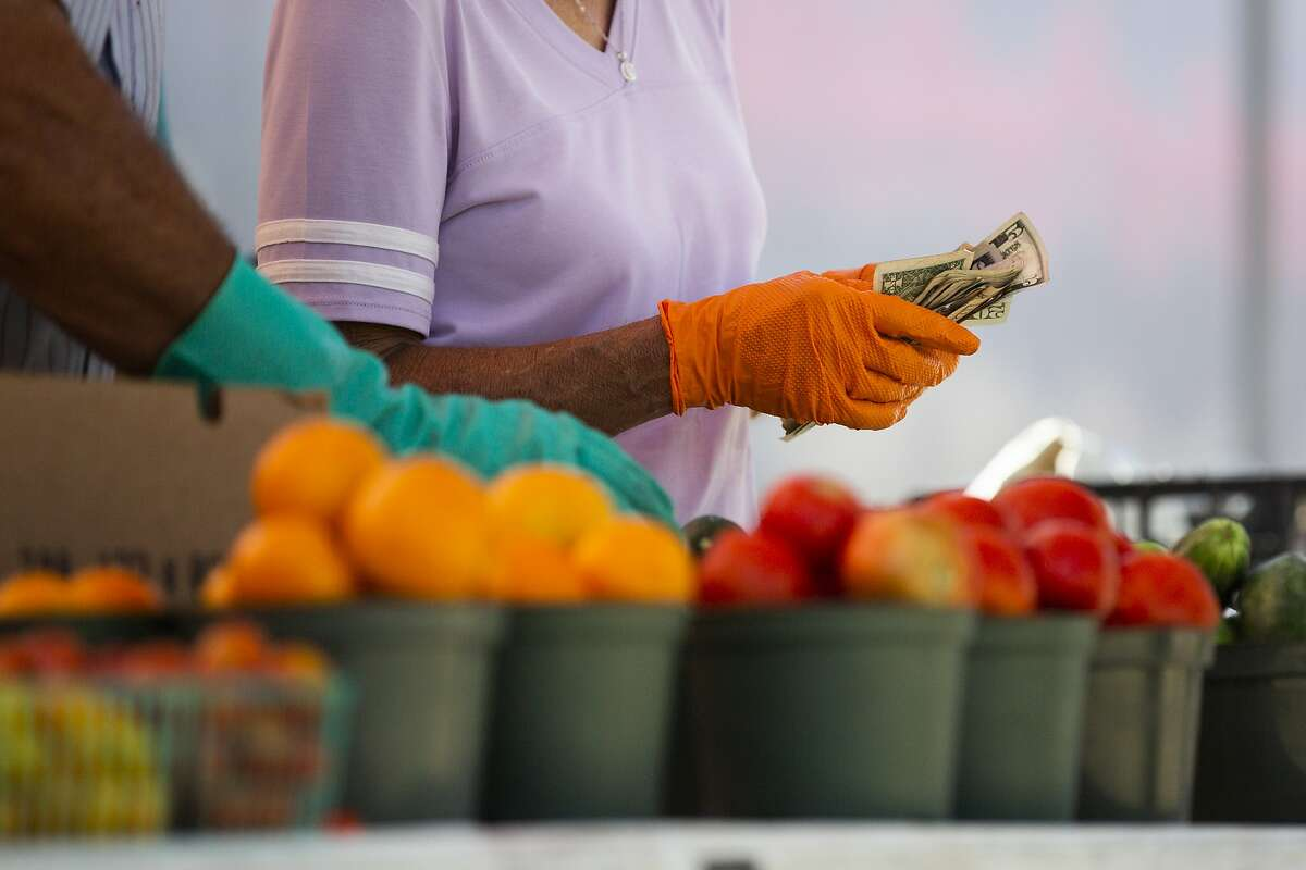 A vendor at the Urban Harvest Saturday Farmers Market in Houston wears gloves as she handles cash during a sale on Saturday, June 6, 2020, in Houston.