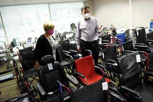Dr. Stephanie Paulmeno , President and CEO of the Connecticut Nursing Association, and Wheel It Forward Founder and CEO Elliot Sloyer look over the donated durable medical at the Government Center in Stamford, Conn. Monday, Dec. 14, 2020. Wheel It Forward allows people to rent donated durable medical equipment such as hospital beds, wheelchairs, walkers, and more.