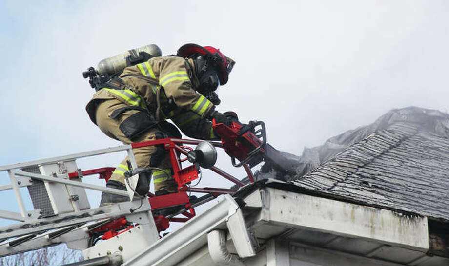 A firefighter working from an aerial ladder clears out debris and cuts a hole in the roof for ventilation at a house fire in the 600 block of Ridge late Thursday morning. The Alton, Godfrey and East Alton fire departments responded to the fire, which appeared to be in the upper floor and attic of the building. No injuries were reported.