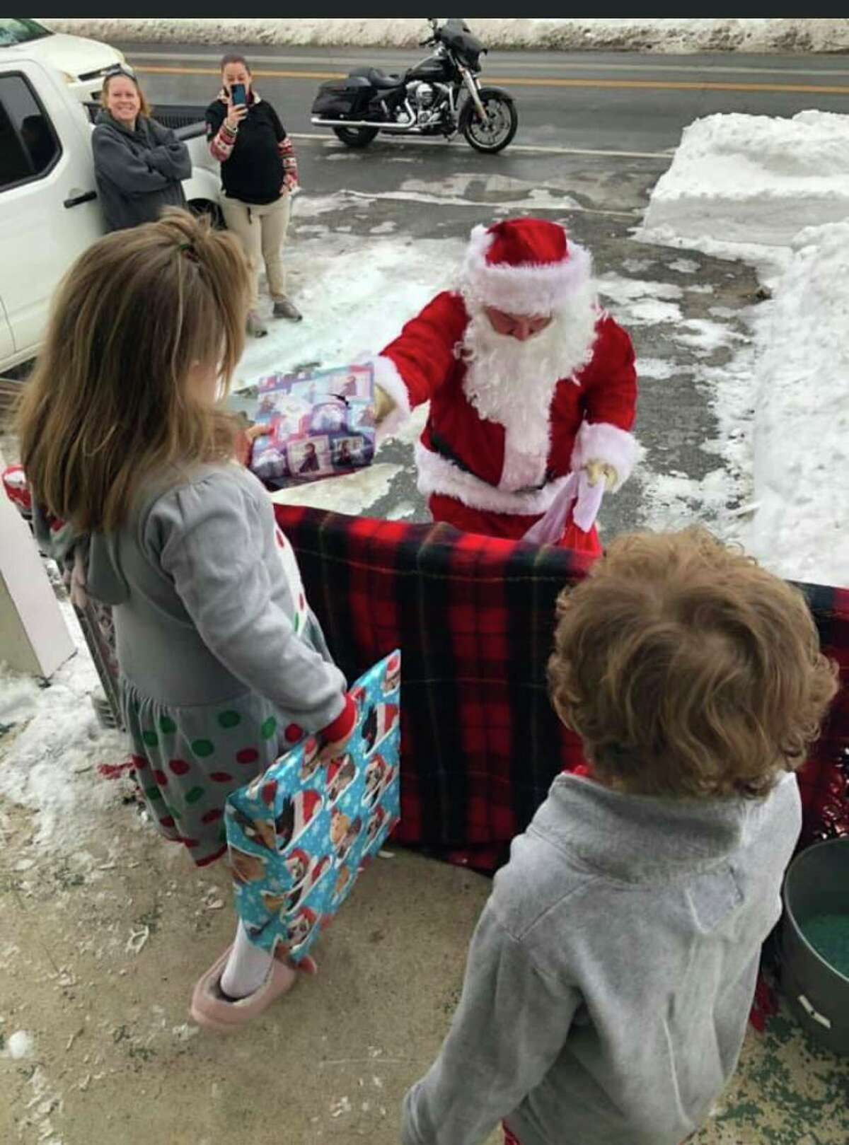 Santa Claus hands out gifts to the youngest members of the Trujillo family.
