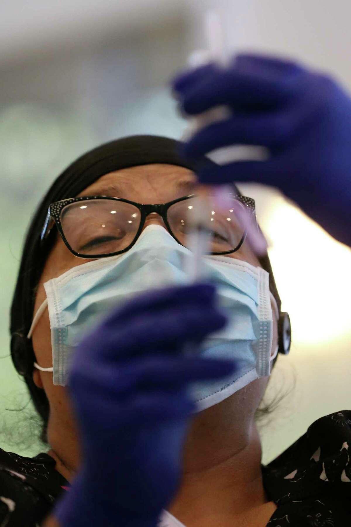 Mirta Martinez measures a dose of the Moderna COVID-19 vaccine.