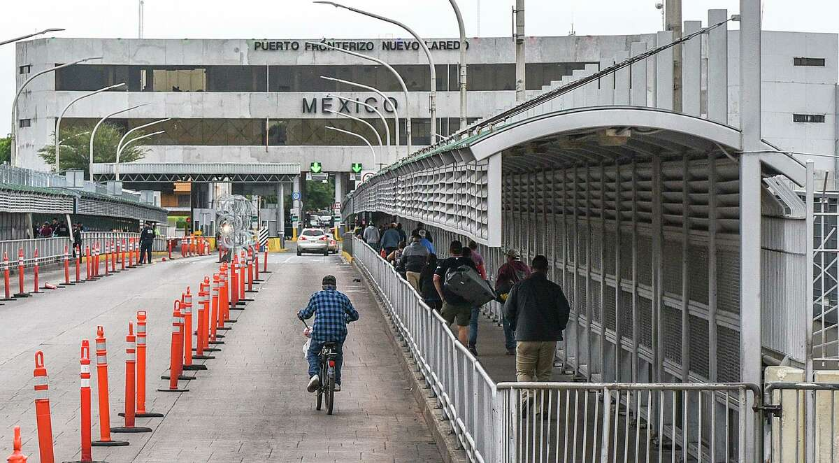 Pedestrians, motorists and cyclists cross the Gateway to the Americas International Bridge, Friday, Mar. 20, 2020, after travel restrictions were announced at the U.S.-Mexico border amid concerns of COVID-19 Coronavirus spreading.