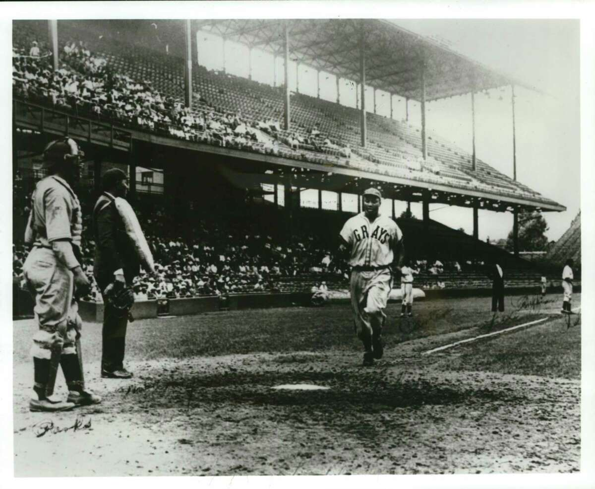 """Josh Gibson, often called """"the black Babe Ruth,"""" scores against the Newark Eagles in 1942. Gibson may be the greatest home run hitter of all time. At long last, his accomplishments, and those of other Negro Leagues players, will be elevated to Major League status."""