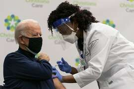 President-elect Joe Biden receives his first dose of the coronavirus vaccine from Nurse partitioner Tabe Mase at Christiana Hospital on live television in Newark Del., Monday, Dec. 21, 2020. (AP Photo/Carolyn Kaster)