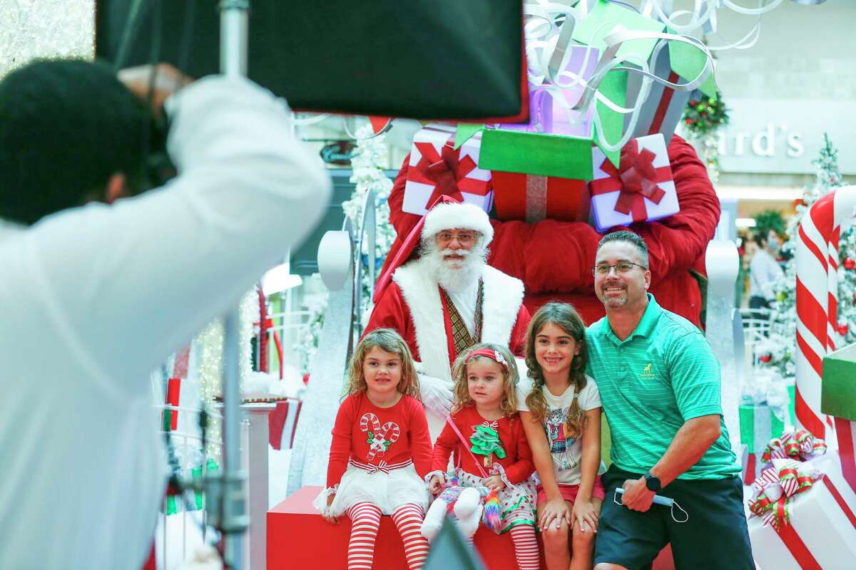 Shelby, 4, (l-r), Delaney, 2, Lacey, 7, and Steven Dolgener have their photo taken with Santa before doing their last minute shopping at Memorial City Mall Wednesday, Dec. 23, 2020, in Houston.
