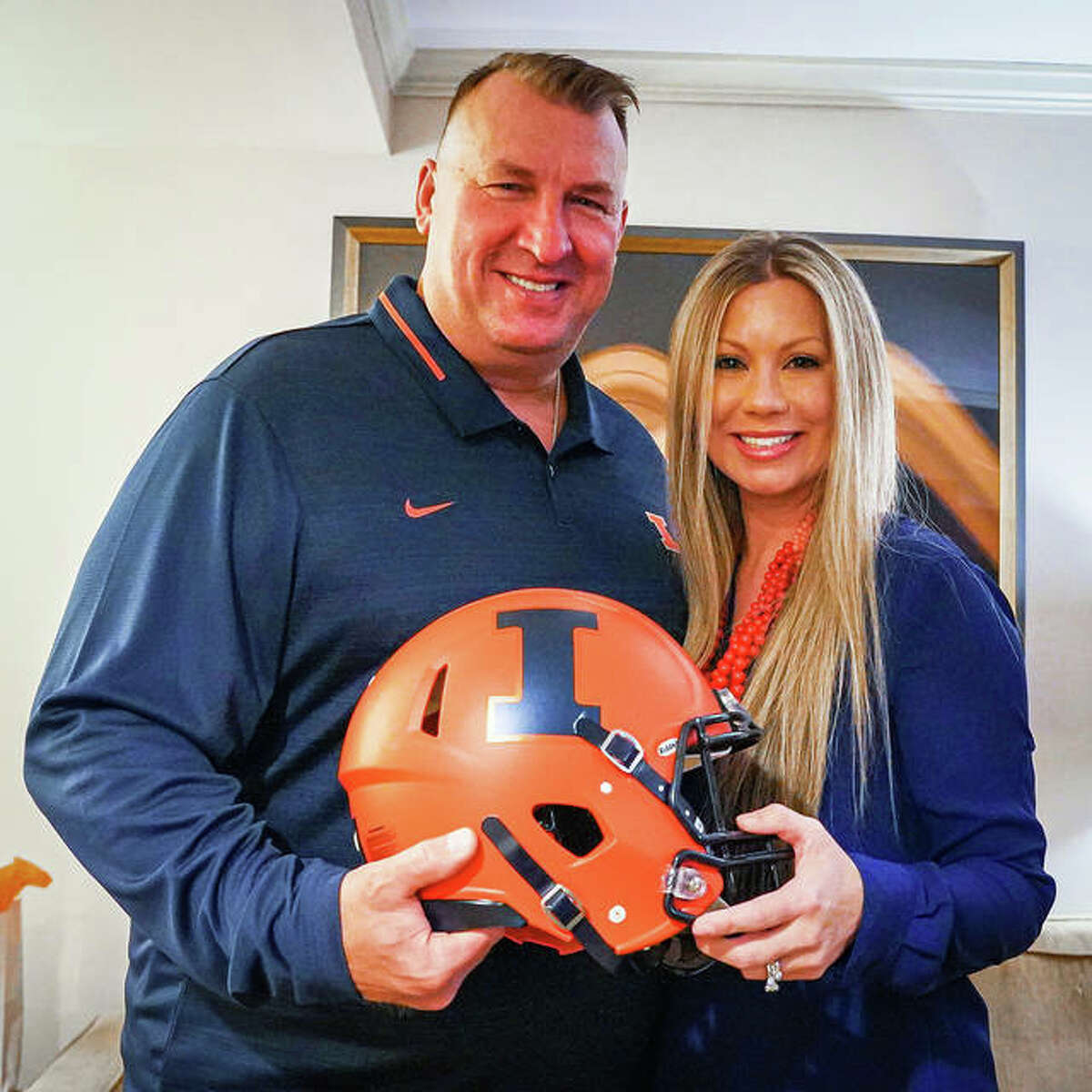 Bret Bielema and his wife Jen pose with an Illinois helmet after arriving in Champaign following the weekend announcement that Bielema has been hired as the Illini's new coach.
