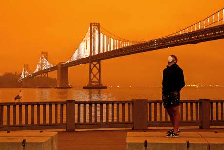 Eli Harik of San Francisco wears a mask while looking up at the dark orange sky hanging over the Embarcadero in downtown San Francisco, Calif. Wednesday, September 9, 2020 due to multiple wildfires burning across California and Oregon.