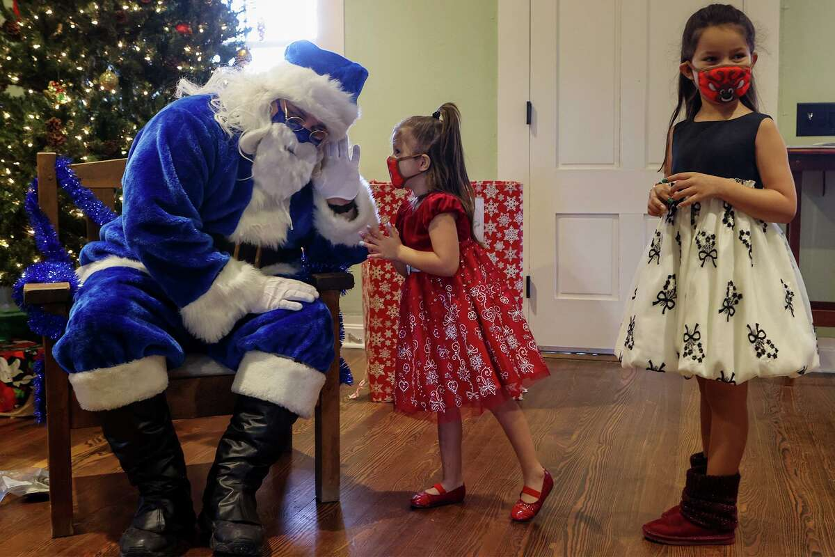 Jordyn Gates, 4, gives her wish list to Blue Santa while her sister, Johanna Gates, 7, waits for her turn at