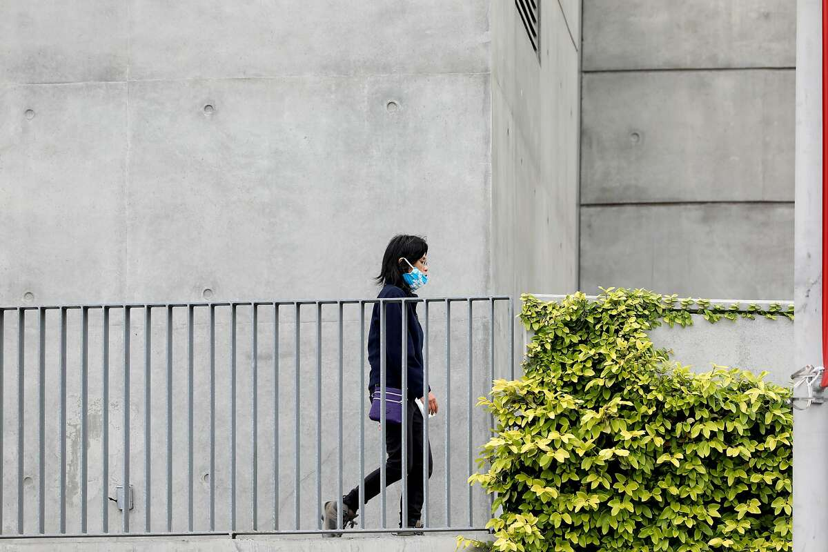 """A woman dons a mask as she walks at The Cathedral of Christ the Light on Friday, April 17, 2020, in Oakland, Calif. Roman Catholic Diocese of Oakland said Dec. 20 a priest has been stripped of his position in Oakland following allegations of """"boundary violations with an adult man."""""""