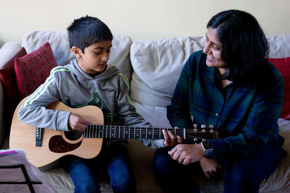 UCSF physician Dr. Madhavi Dandu sings along while her son Arshan, 9, plays guitar at their home in San Francisco, Calif. Tuesday, December 22, 2020. Dandu was one of the first to receive the Pfizer COVID-19 vaccine at UCSF, where she works as a physician. Her husband Nima Afshar, an ER doctor at the San Francisco VA Medical Center, will be getting the Moderna vaccine this week.
