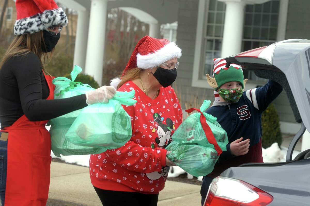 Shelton Senior Center director Doreen Laucella, center, assistant director Shauna Dumas, left, and volunteer elf Tyler Kudej put bagged holiday meals into the trunk of a waiting car during the curbside event in front the center in Shelton, Conn. Dec. 24, 2020.