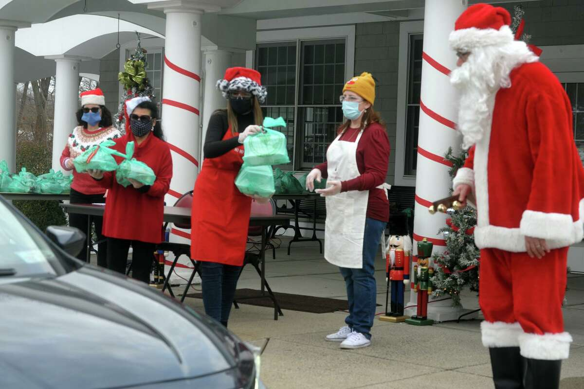 Staff and volunteers of the Shelton Senior Center and Echo Hose Hook, Ladder and Ambulance handed out bagged holiday meals to seniors during a curbside event in front the center in Shelton, Conn. Dec. 24, 2020.