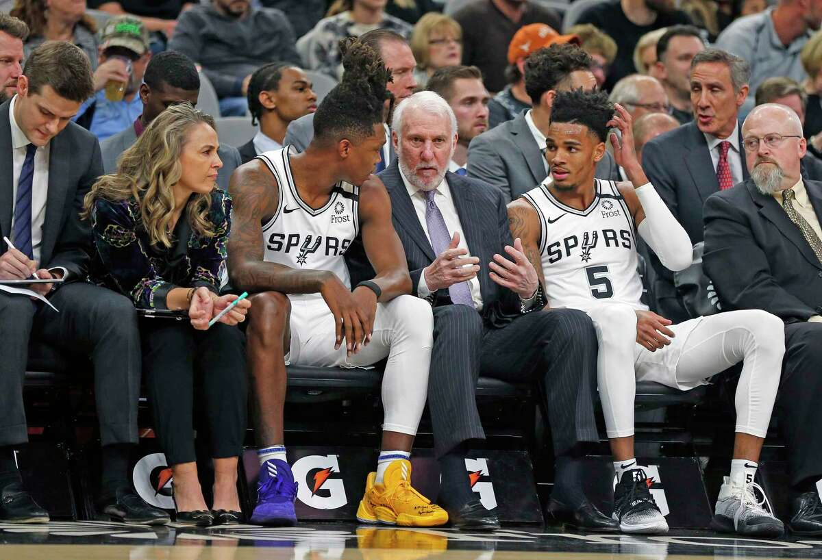 Gregg Popovich, center, is 71 but finds ways to connect with young players such as Lonnie Walker IV, 22, left, and Dejounte Murray, 24, by inquiring about their tastes in music. On practice days, players and staff members take turns choosing the soundtrack of the day, whether it's classical music or hip hop.