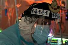 HOUSTON, TX - DECEMBER 22: (EDITORIAL USE ONLY) Dr. Joseph Varon watches the endoscope screen while performing a tracheotomy procedure on a patient in the COVID-19 intensive care unit (ICU) at the United Memorial Medical Center on December 22, 2020 in Houston, Texas. According to reports, Texas has reached over 1,610,000 cases, including over 26,190 deaths. (Photo by Go Nakamura/Getty Images)