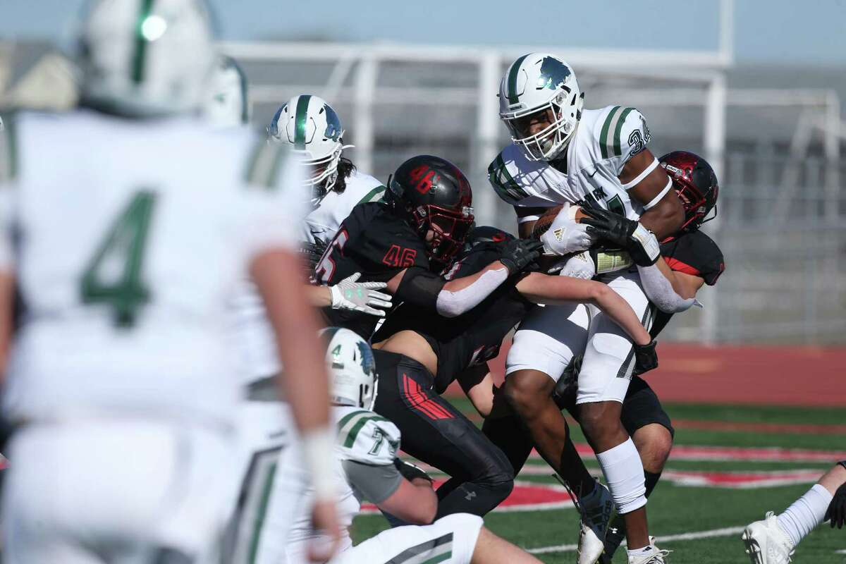 Cougar defenders struggle to bring down Timberwolves receiver Josh Cameron as New Braunfels Canyon plays Cedar Park at Canyon High School in high school football playoffs on Dec. 24, 2020.