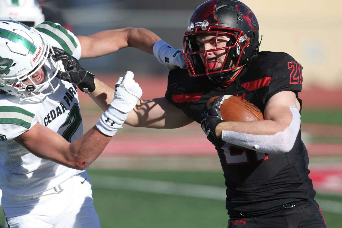 New Braunfels Canyon running back Micah Williford, who had 44 yards rushing and 88 yards receiving with a touchdown, battles a Cedar Park tackler on a run on Thursday.