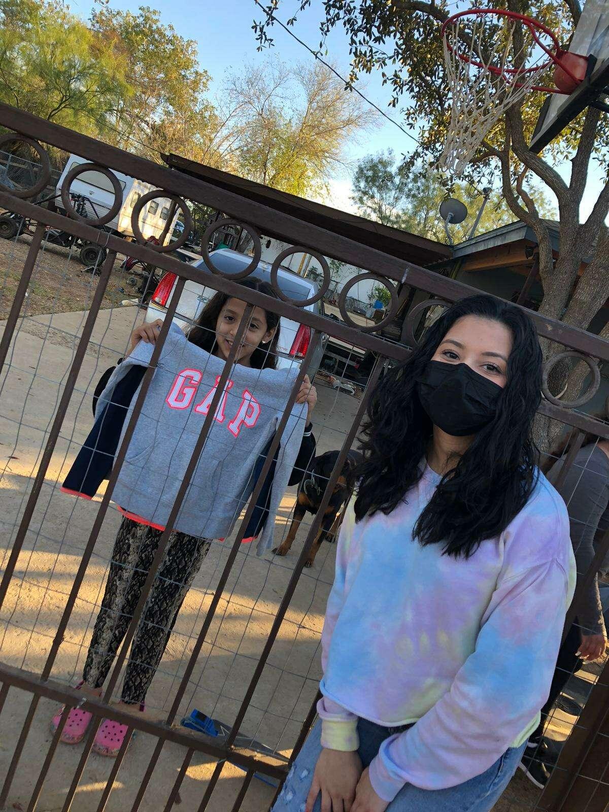 Una niña sonríe al mostrar su hoodie entregada por Anacecy Chávez, embajadora juvenil de la organización PAME Kids USA, durante un evento de donación celebrado recientemente en El Cenizo y Río Bravo.