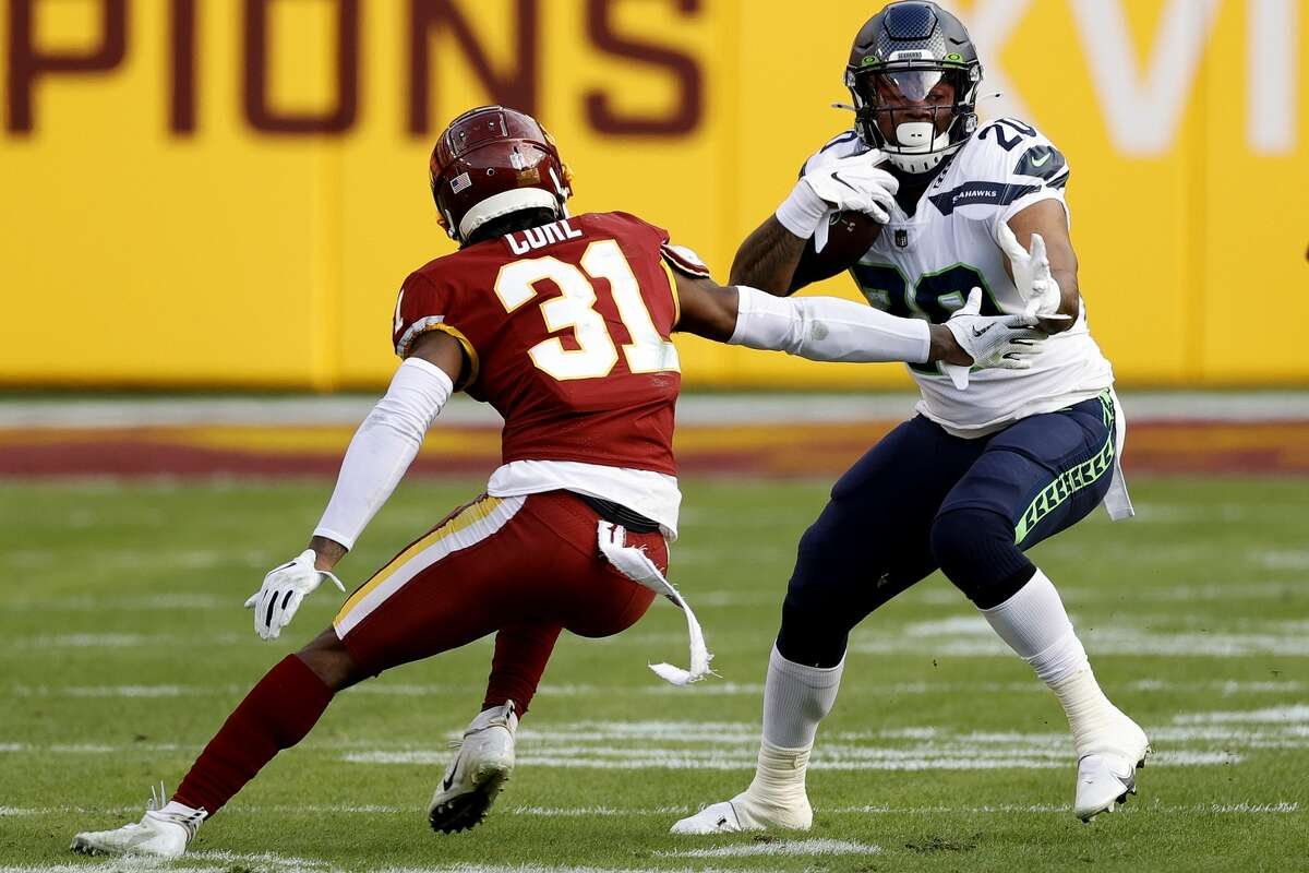 LANDOVER, MARYLAND - DECEMBER 20: Rashaad Penny #20 of the Seattle Seahawks breaks a tackle attempt by Kamren Curl #31 of the Washington Football Team at FedExField on December 20, 2020 in Landover, Maryland. (Photo by Tim Nwachukwu/Getty Images)